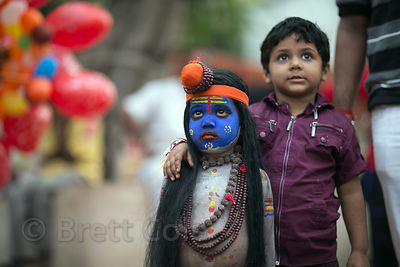 A middle class Indian boy poses with a dalit boy dressed as Shiva to pose for photos with tourists during the Pushkar Camel Fair, Pushkar, Rajasthan, India