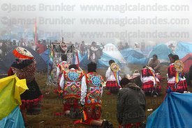 Dance group praying in morning mist in campsite during Qoyllur Riti festival, Peru