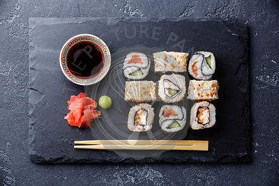 Sushi rolls Yin Yang shape on stone slate on black stone background