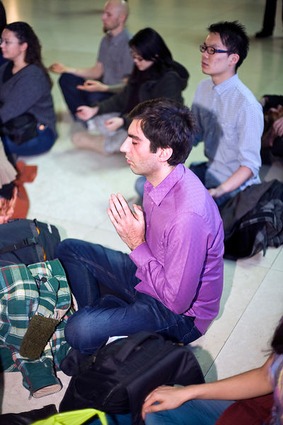 UK - London - A man taking part in a meditation flash mob in the Great Court of the British Museum