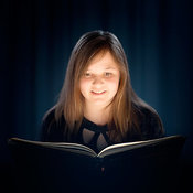 Young girl reading a book in dark room