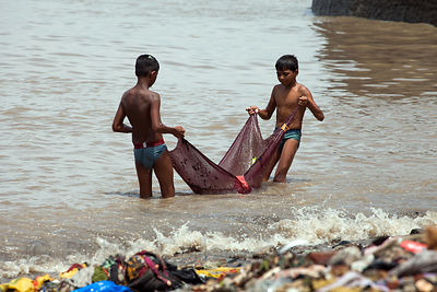 Boys from the Colaba fishing village in Mumbai, India haul in a net full of garbage. The boys bring the net back and dump it in an old wooden boat, then frantically sift through the garbage to yield an average of two or three tiny fish per net.