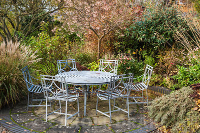 Seating area in the back garden surrounded by shrubs and grasses including Stipa gigantea, miscanthus, viburnum and sorbus. Windy Ridge, Little Wenlock, Shropshire, UK
