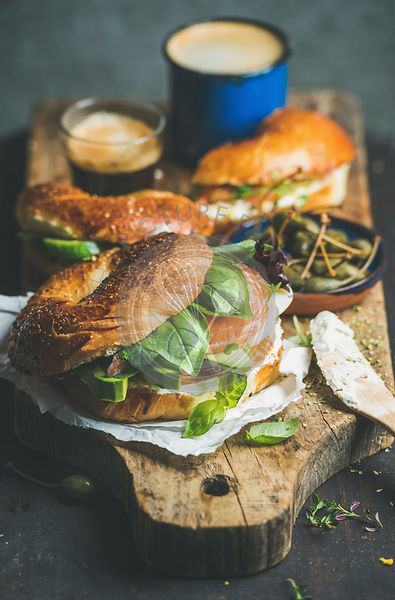 Breakfast with bagels with salmon, avocado, cream-cheese, basil, espresso coffee, capers on rustic wooden board