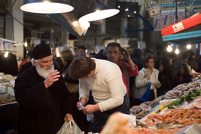 Greece - Athens - A Greek Orthodox priest blesses a fishmonger as he buys seafood from a stall in the Athens Central Market on Athinas Street