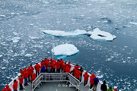 Passengers of National Geographic Explorer looking at the landscape of  aquamarine icebergs from the deck of National Geographic Explorer.