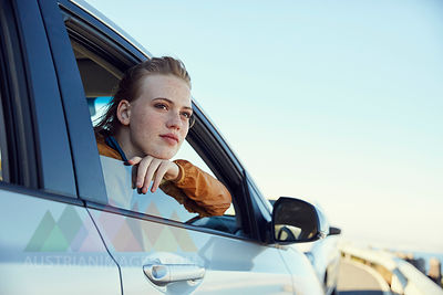 Young woman looking out of a car