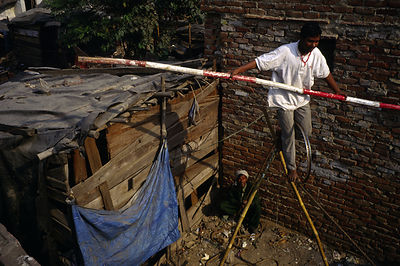 India - New Delhi - A performer practices his tightrope walking (or high-wire) act in the slums of Shadipur.
