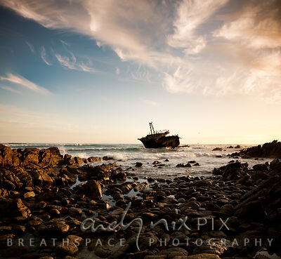 Wreck of the Misho Maru 38 at Cape Agulhas, used by cormorants and other sea birds as a safe roosting ground, rocks in the foreground.