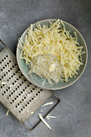 Ceramic Bowl of Shredded Cheese with Vintage Cheese Grater, Photographed on grey background from top view.