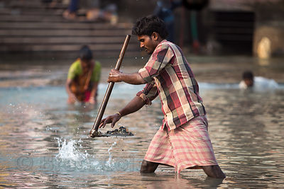 A man searches for money among debris in the Ganges river, Haridwar, India