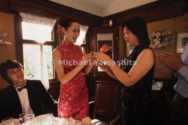 The bride receives a special gift from her mother at a wedding banquet in Shanghai, China.