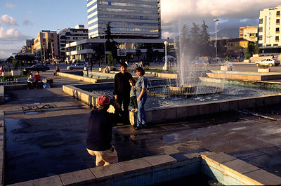 A family have their photograph taken in the centre of Tirana
