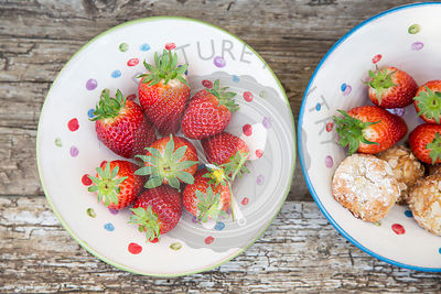 whole strawberries in spotted ceramic rustic bowl, with almond cookies on rustic wood table