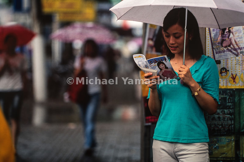 Young lady walking on the street with an umbrella in Shanghai, China.