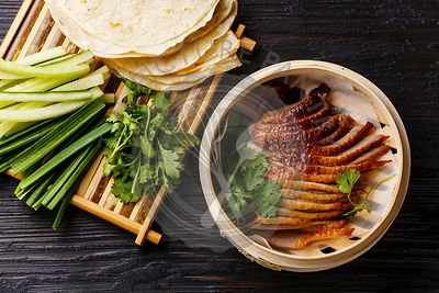 Peking Duck in bamboo steamer served with fresh cucumber, green onions, cilantro and roasted wheaten chinese pancakes on black burned wooden background
