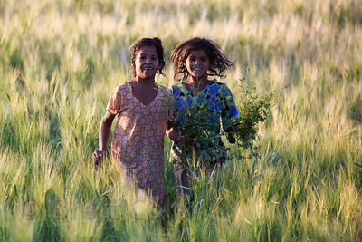 Girls run through a flower field (in which they work) in Surajkund village, Rajasthan, India