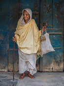 An old widow gets ready to go to the Gopinath temple to play holi in Vrindavan.