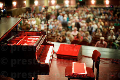 Grand Piano on Stage with Audience Seated in the Auditorium