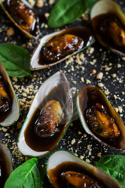 Asian dish - mussels in sticky sweet saucem with peanuts, on slate board