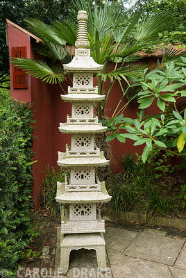 Chinese granite pagoda in the Red Wall garden planted around with palm Trachycarpus wagnerianus and Edgeworthia chrysantha. Beggars Knoll, Newtown, Westbury, Wiltshire, UK