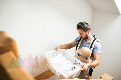 Father with baby in baby carrier carrying laundry basket walking upstairs