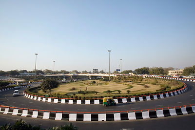 India - Delhi - Boys play cricket on a gardened Traffic Island