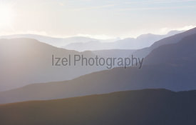 The warm sun creeping in on a misty cold morning over the ridge lines of the Derwent Fells in the English Lake District, UK.
