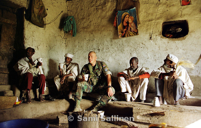 A Dutch peacekeeper drinks suwa, the Eritrean homemade beer, with Orthodox Christian priests..Photo by: Sami Sallinen
