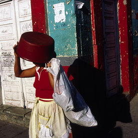 A woman uses a bowl to shield her from the sun, Tegucigalpa, Honduras