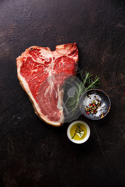 Raw Dry Aging Steak meat T-bone and seasoning on dark background