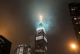 The top of the Met Life Tower in fog at night near the intersection with East 23rd Street, across from Madison Square Park in Manhattan, New York City.
