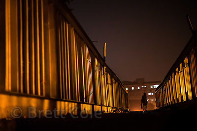 A man crosses a dramatically lit footbridge at night, over the railway tracks and busy Strand Road, near Barabazar, Kolkata, India.