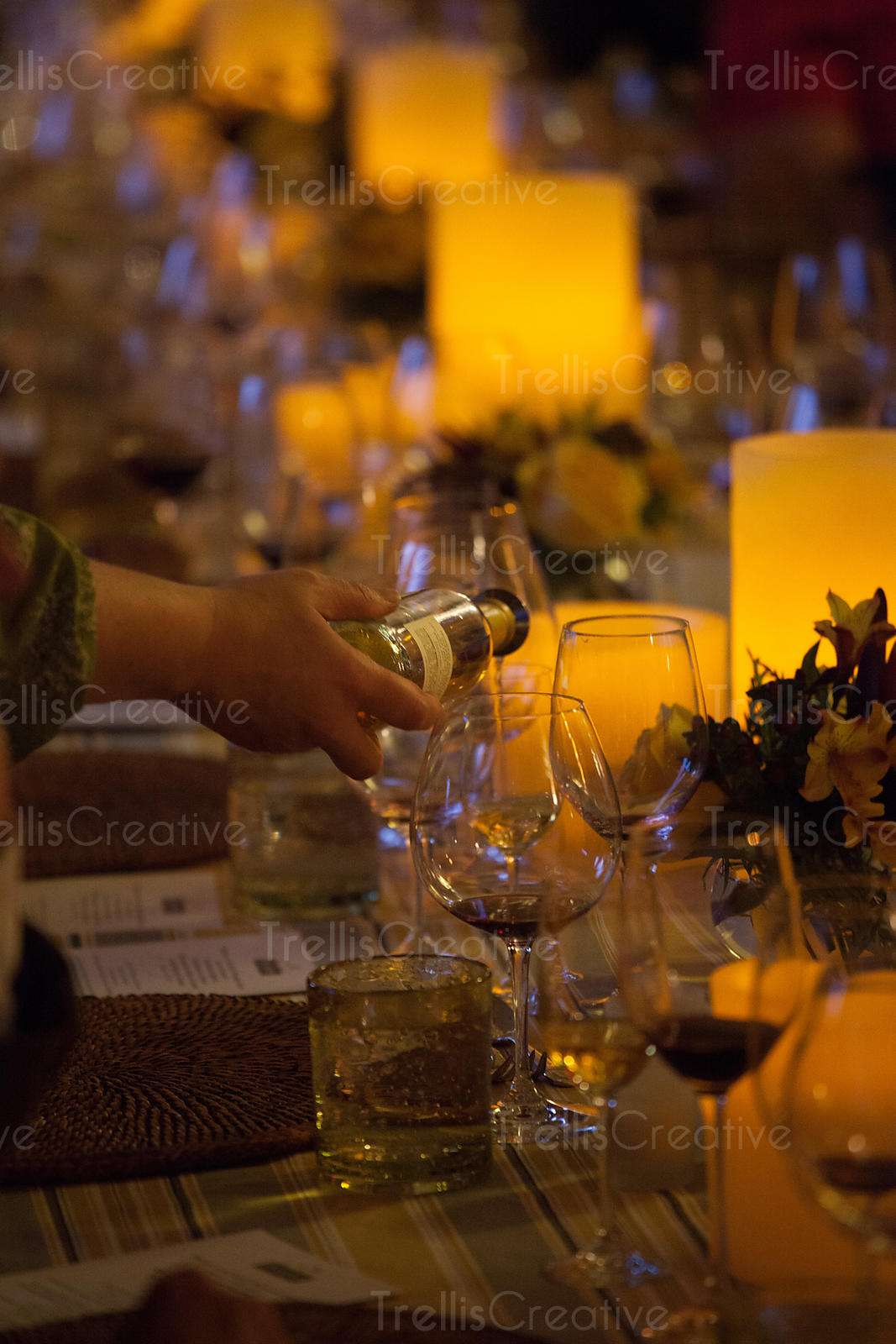 Wine being poured into empty glasses on a warmly candlelit dinner table