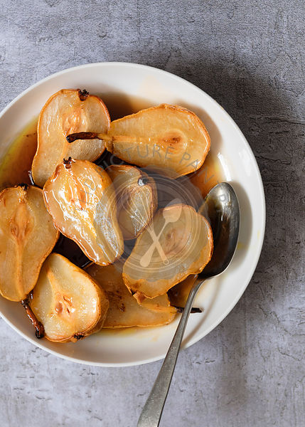 Maple and cinnamon roasted pears in a bowl.