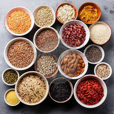 Superfoods and cereals selection in bowls: quinoa, chia, goji berry, mung bean, buckwheat, bean, turmeric, polba, bulgur, lentil, sesame, flax seed, wild rice, almond on gray concrete background