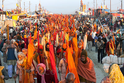 Orange-robed sadhus walk to a dinner tent at the 2013 Kumbh Mela, Allahabad, India.