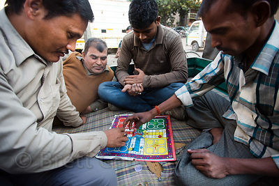 Men play Pachisi, or Cross and Circles, a traditional Indian board game that is the basis for the well-known board game Parcheesi, in the back of a pickup truck in Delhi, India