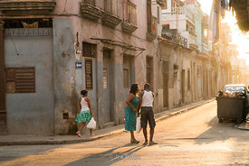 People crossing a street at sunrise in Havana, Cuba.