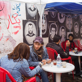 Couples sit at pavement cafe called the Revolution of the 25th of January in the Bourse area of Cairo. Behind them are graffiti portraits of young men killed in the fighting, Cairo