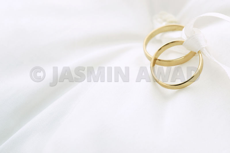Wedding rings on ring pillow with copy space