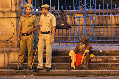 A Sadhu sits next to police officers at night, Babughat, Kolkata, India