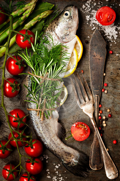Raw rainbow trout with lemon, herbs and spice on rustic background