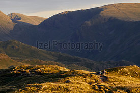 Two hikers returning from an evenings walk in the English Lake District at sunset. UK