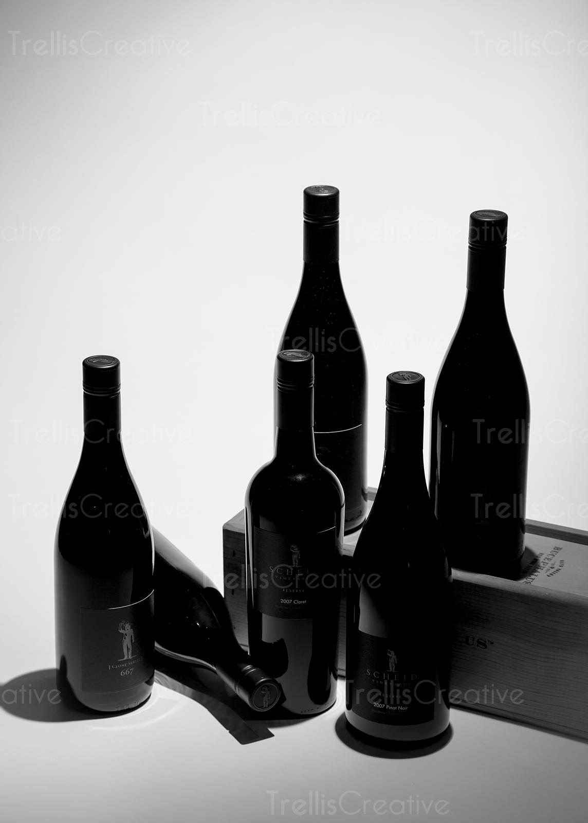 Silhouette of six wine bottles photographed with a wooden box
