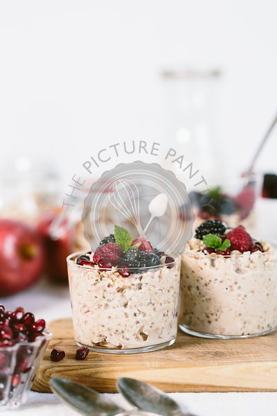 2 Clear glass Bowls of apple muesli topped off with berries are photographed from the front view.