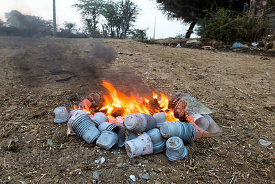 Plastic chai tea cups burn in a fire to keep people warm on a cold winter morning in the desert, Majhewla village, Rajasthan, India. Such fires, numbering in the millions every day across India, contribute to the country's terrible air pollution.