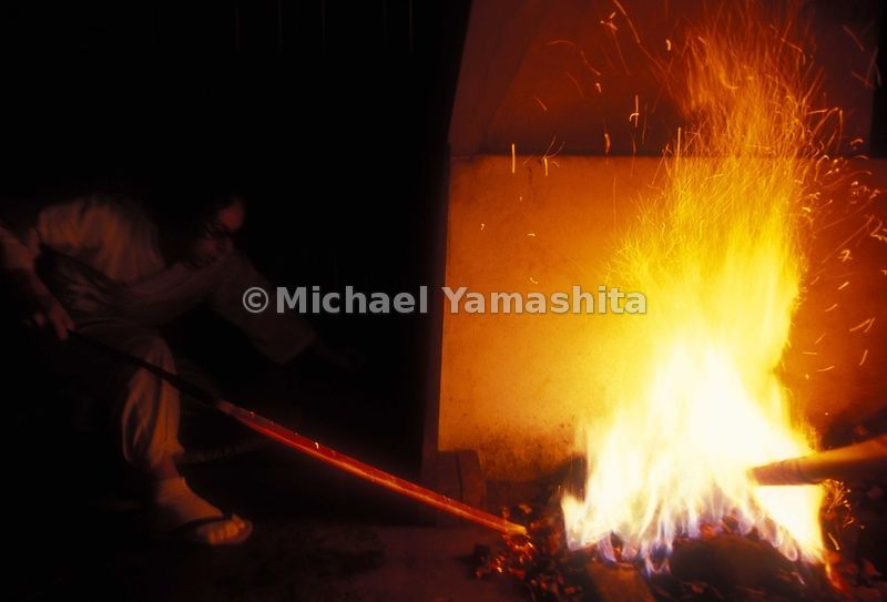 Master sword maker placing metal in the fire. Nara
