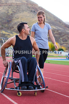 Man in a wheelchair exercising on an accessible track in Colorado Rocky Mountains with attractive female