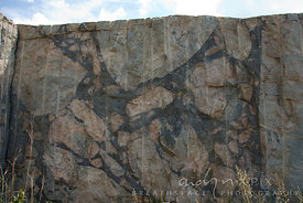 Quarried granite showing a cross section of different coloured embedded rock boulders.